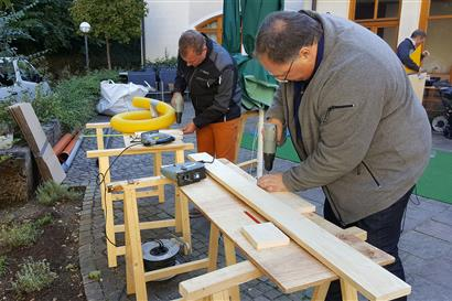 Men drilling into wooden boards with a drill