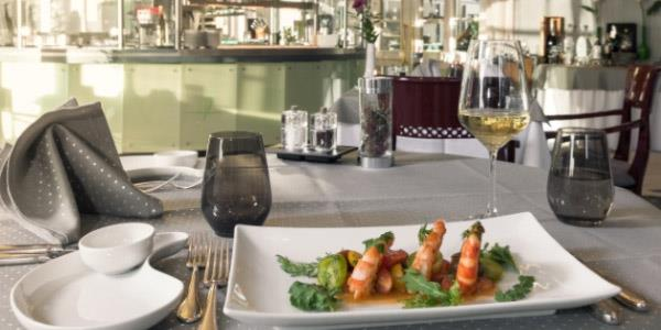 Shrimps on plate with rocket, cutlery and glasses next to it