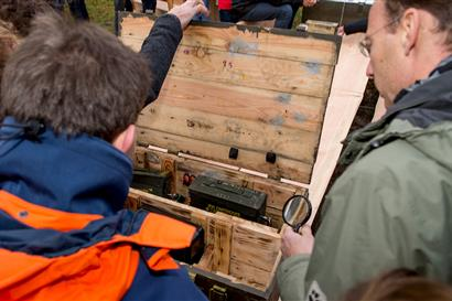 Men open a wooden box