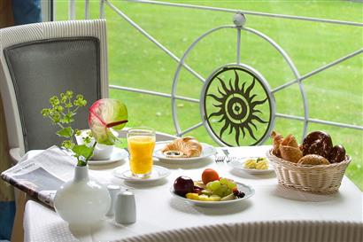 Breakfast table with crossaint, pastries, fruits and orange juice