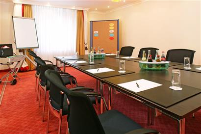Seminar room with flipchart, pinboard, chairs and drinks on the tables