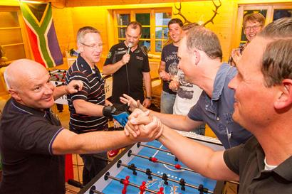 Men play table football and congratulate each other