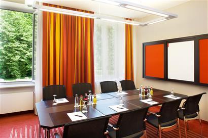 Tagungsraum mit Tischen, Stühlen und Pinnwand