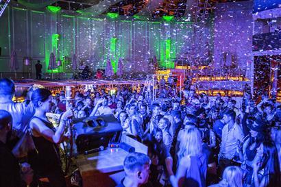 Menschen in einem Saal mit Konfetti in der Luft